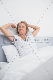 Blonde woman stretching and looking away in bed in the morning