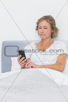 Blonde woman sending text message in bed