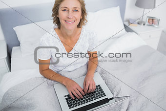 Smiling blonde woman in bed using her laptop