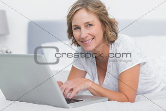 Smiling blonde woman lying on bed using laptop