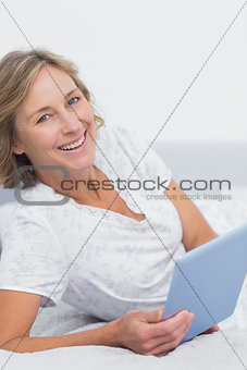 Smiling blonde woman lying on bed using tablet pc