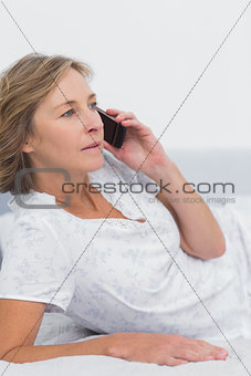 Blonde woman lying on bed making a phone call