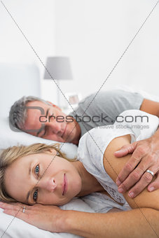 Blonde woman smiling at camera as husband is sleeping