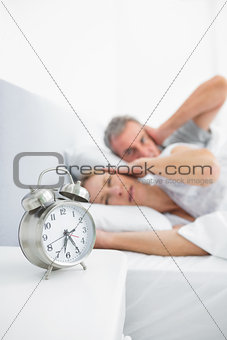 Couple blocking their ears from alarm clock noise