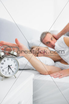 Tired wife turning off alarm clock as husband is covering ears