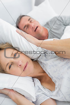 Tired wife blocking her ears from noise of husband snoring looking at camera