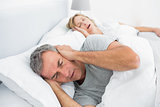 Tired man blocking his ears from noise of wife snoring