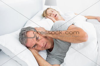 Annoyed man blocking his ears from noise of wife snoring