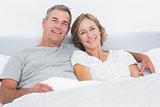 Happy couple cuddling in bed looking at camera