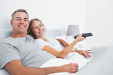 Happy couple cuddling in bed watching television