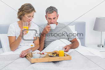 Happy couple having breakfast in bed together