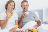 Cheerful couple having breakfast in bed together