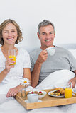 Content couple having breakfast in bed together