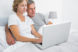 Happy couple using their laptop together in bed
