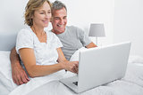 Smiling couple using their laptop together in bed