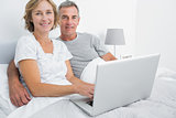Relaxed couple using their laptop together in bed