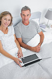 Couple using their laptop together in bed