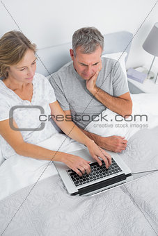 Thoughtful couple using their laptop together in bed