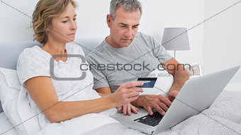 Thoughtful couple using their laptop to buy online