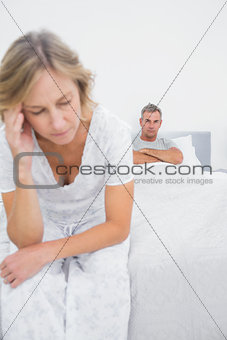 Annoyed couple sitting on opposite ends of bed after a fight
