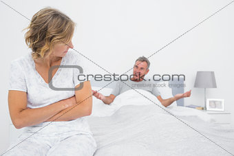 Angry woman looking at husband gesturing during a fight