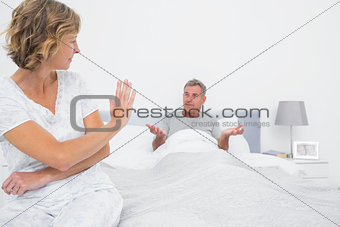 Annoyed woman looking at husband gesturing during a fight