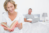 Woman reading book while husband is using laptop