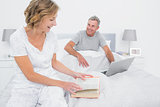 Smiling woman reading book while husband is using laptop