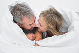 Loving middle aged couple under the duvet