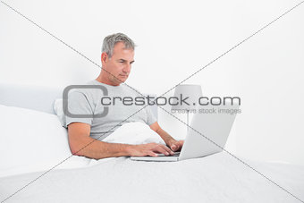 Grey haired man using laptop in bed