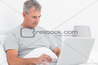 Grey haired man using his laptop in bed