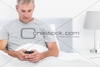 Grey haired man sending a text in bed