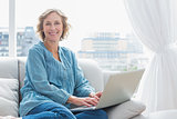 Content blonde woman sitting on her couch using laptop