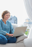 Smiling blonde woman sitting on her couch using laptop