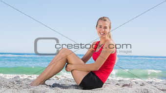 Athletic blonde sitting and smiling at camera