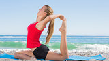 Athletic blonde stretching leg in yoga pose