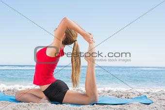 Fit blonde stretching leg in yoga pose