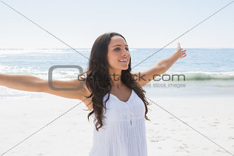 Happy brunette in white sun dress enjoying the sun