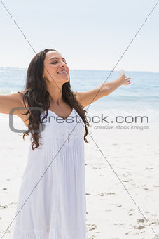 Content brunette in white sun dress enjoying the sun