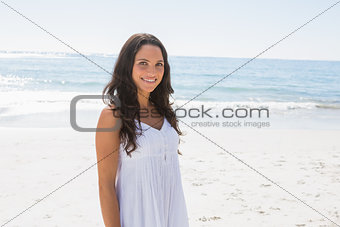 Content brunette in white sun dress looking at camera