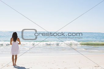 Brunette in white sun dress standing by the water
