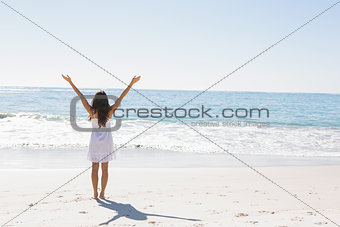 Brunette in white sun dress standing by the water with arms raised
