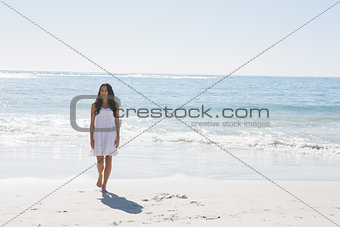Brunette in white sun dress walking from the sea