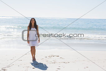 Beautiful brunette in white sun dress walking from the ocean