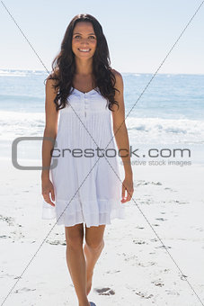 Smiling brunette in white sun dress walking towards camera