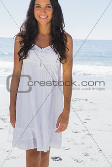 Happy brunette in white sun dress walking towards camera