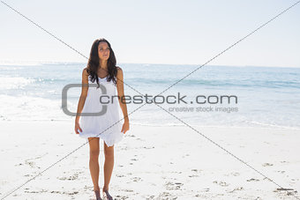 Happy brunette in white sun dress walking on the sand