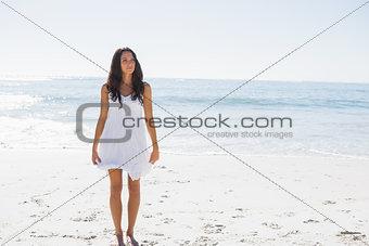 Happy brunette in white sun dress walking on the sand