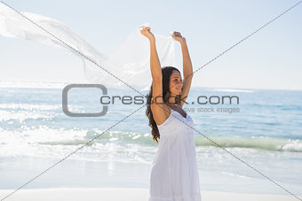 Happy brunette in white sun dress holding sarong