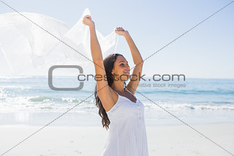 Pretty brunette in white sun dress holding sarong